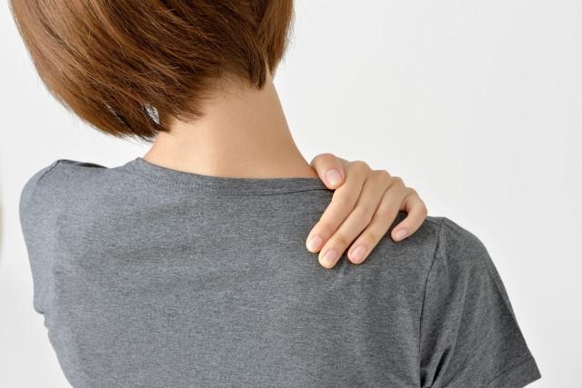 肩を押さえる女性